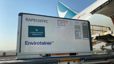 A refrigerated container is ready to be lifted up to the side door of cargo plane.