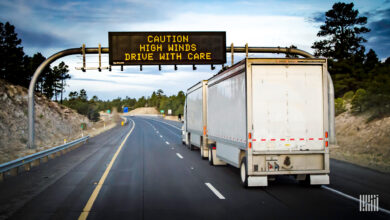 """Tractor-trailer with """"Caution High Winds"""" highway sign ahead."""