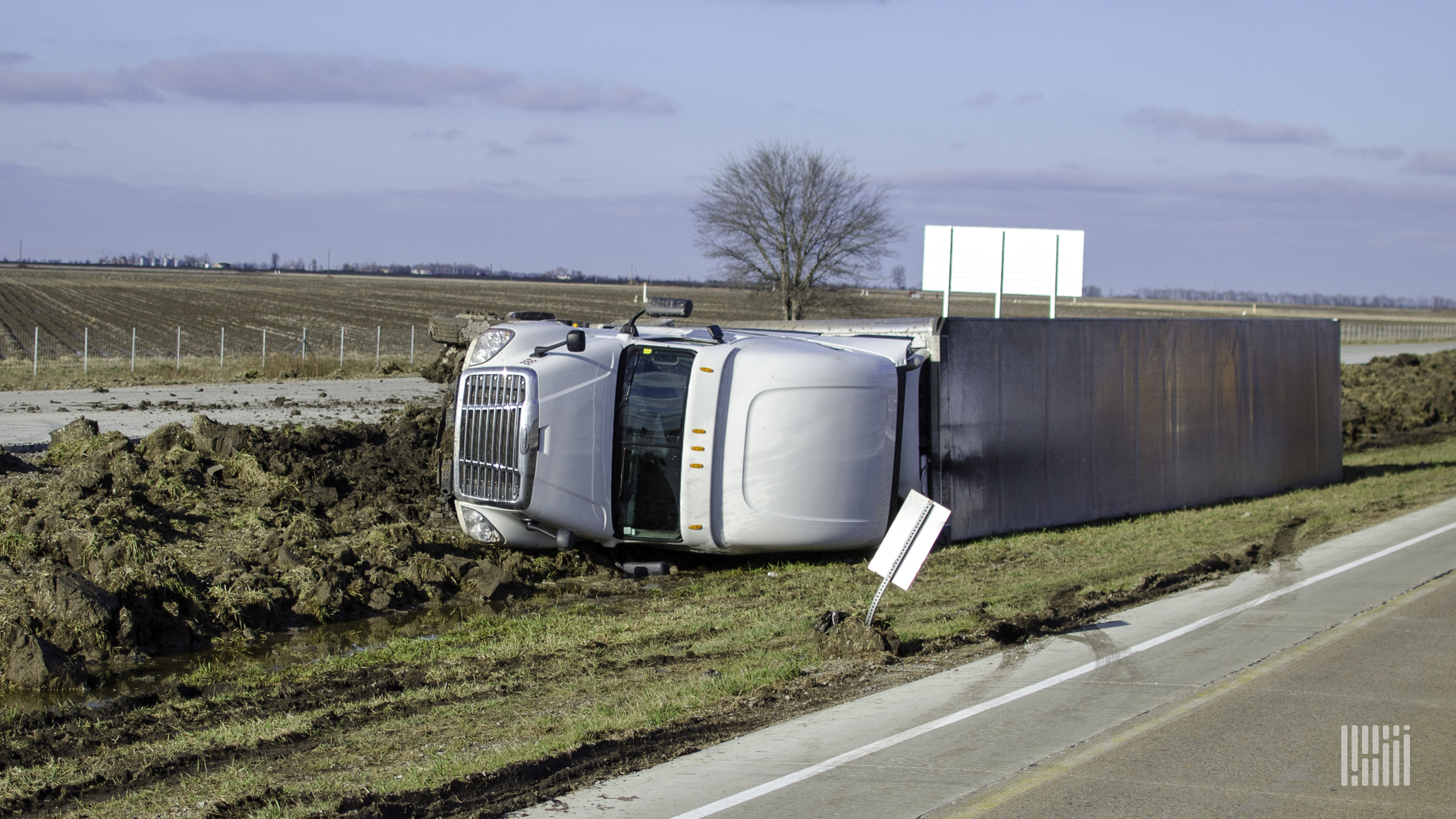 Tractor-trailer flipped on the side of a road.