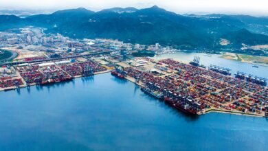 Aerial view of the Port of Yantian in Shenzhen, China, with lots of containers stacked on the wharf.