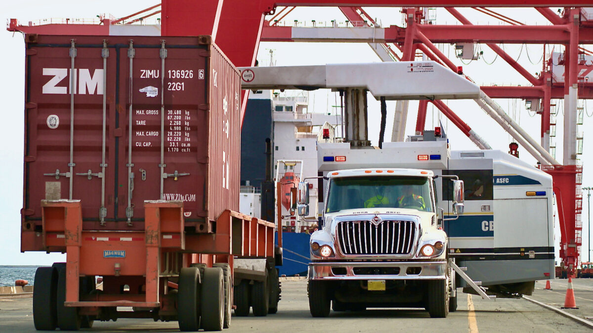 CBSA officers keep watch from a truck as an intermodal container prepares to roll by at a Canadian port.