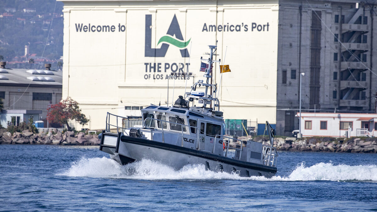 A Port Police patrol boat passes a huge sign painted on the side of one of the port buildings. (Photo: Port of Los Angeles)