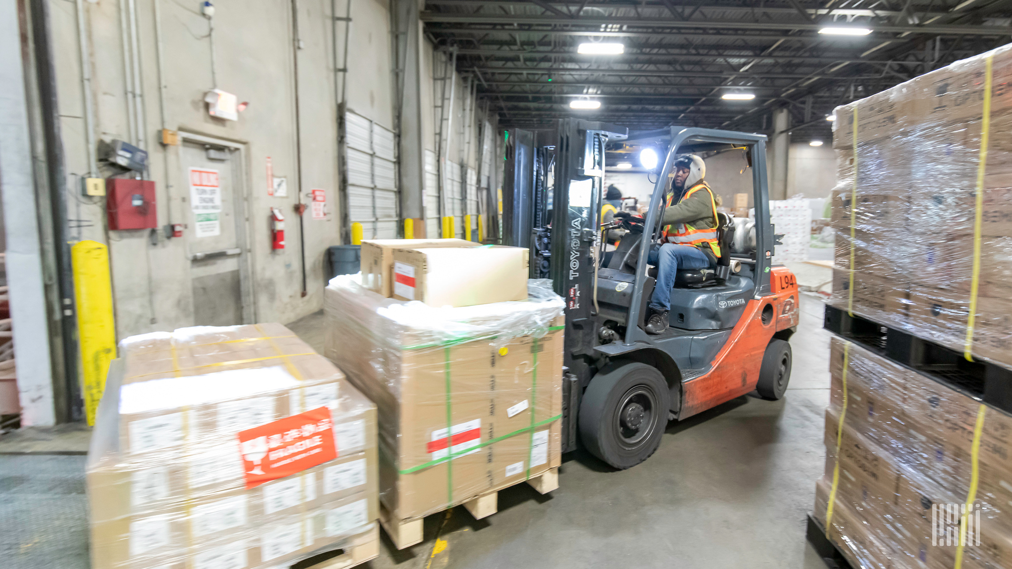 A forklift moves wooden pallets of goods at an airfreight warehouse.