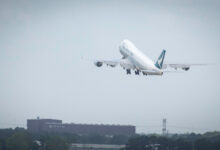 A jumbo jet takes off into a gray sky. View from behind.