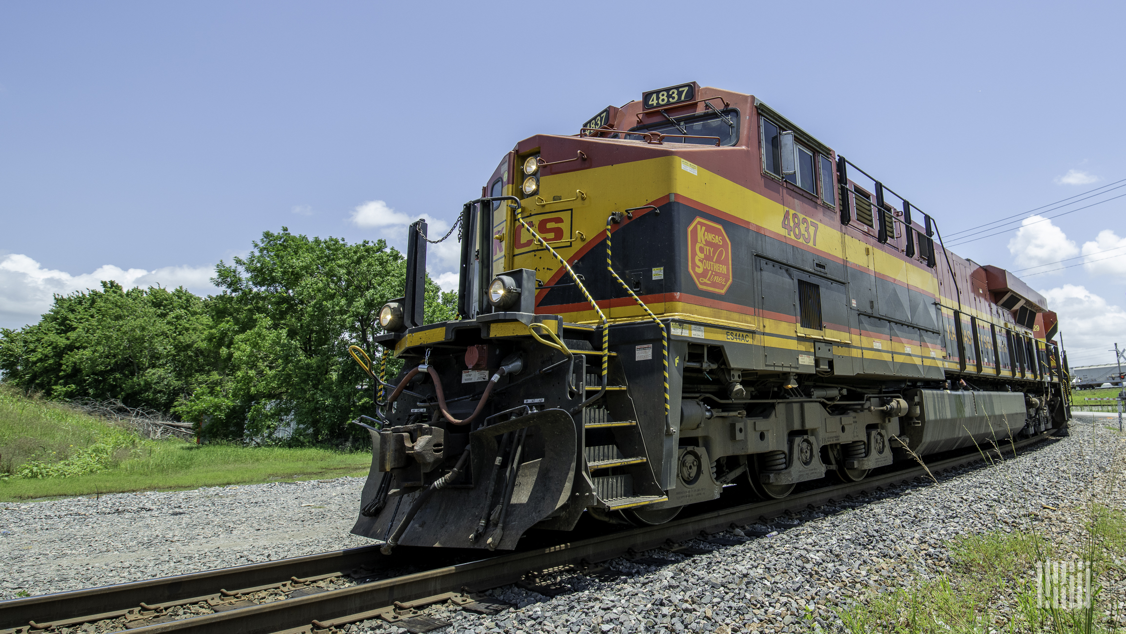 A photograph of a Kansas City Southern locomotive rolling down a train track.