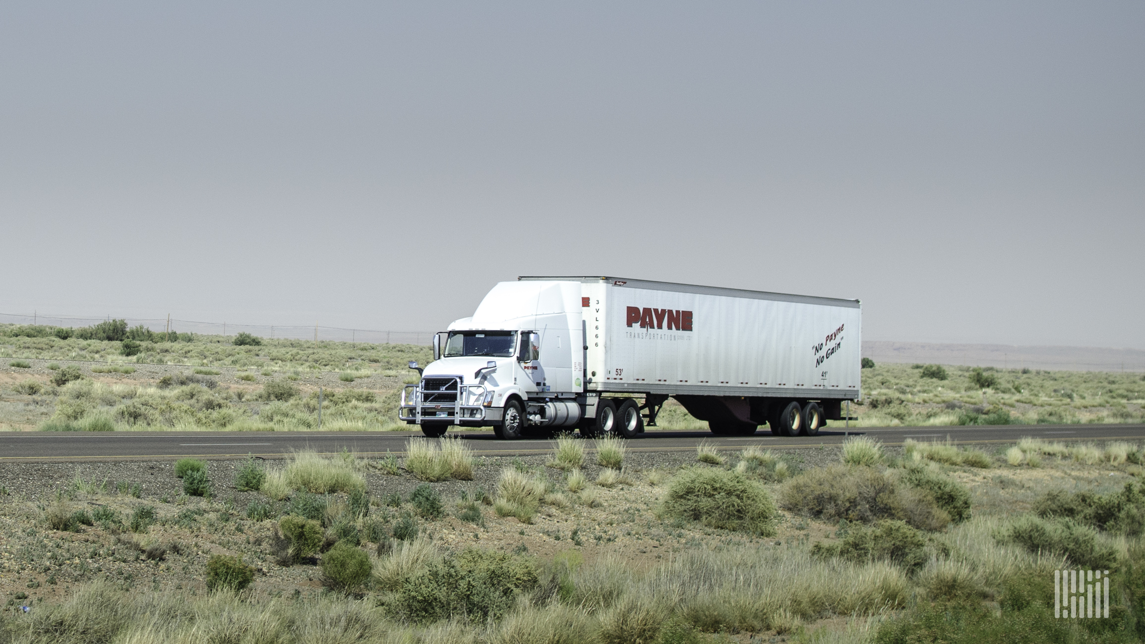 A tractor-trailer of Mullen Group trucking company Payne viewed from the side of a road.