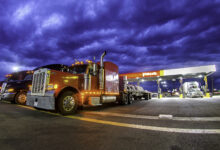 Trucks parked at a Pilot truck stock at night-time.