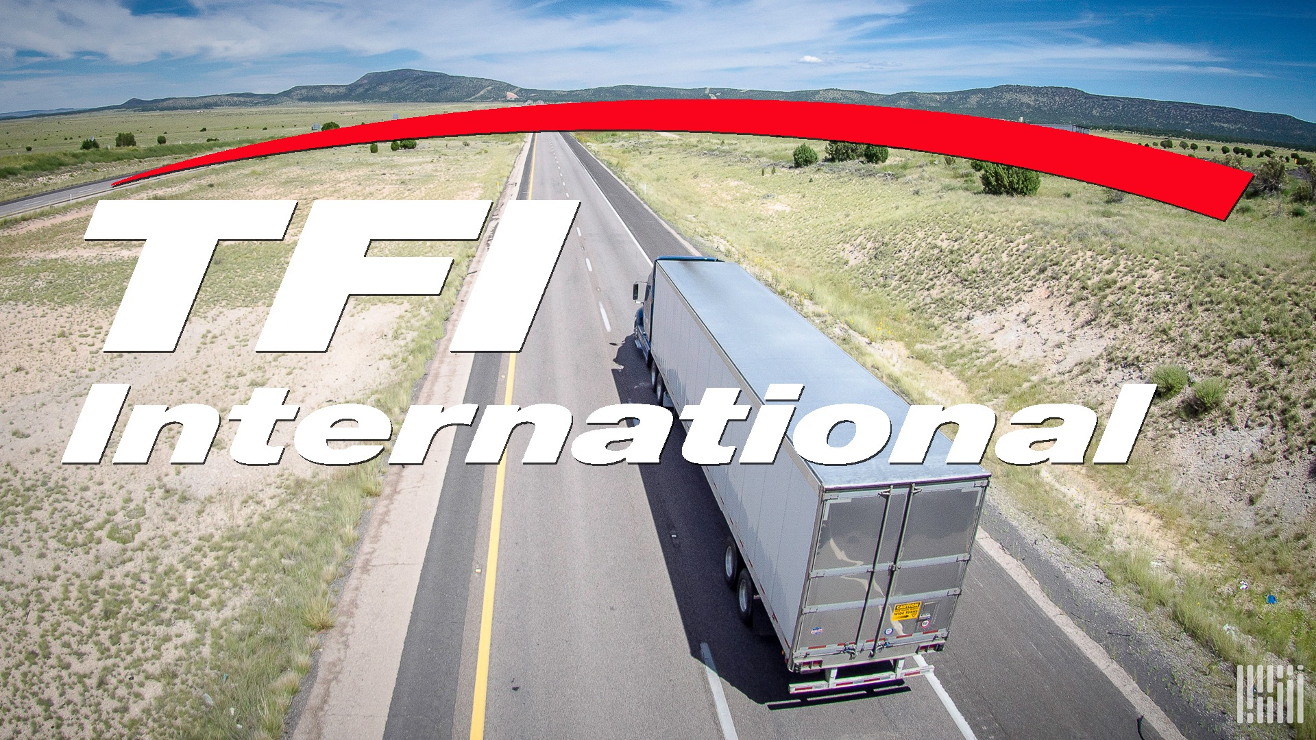A commercial truck seen from behind travels on a highway with the logo of TFI International layered on top of the image.