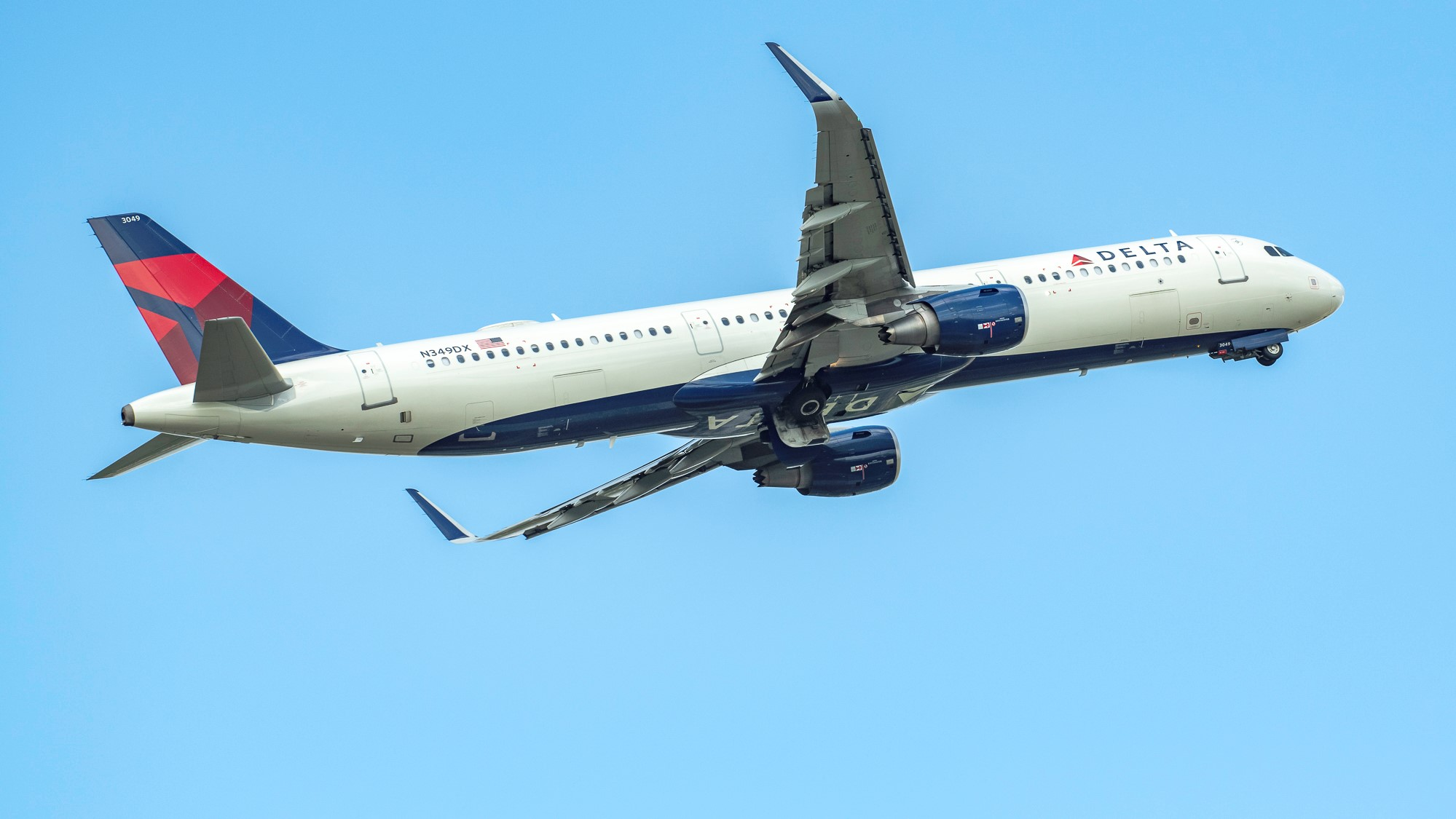 A Delta jet banking in the blue sky, view from underneath.