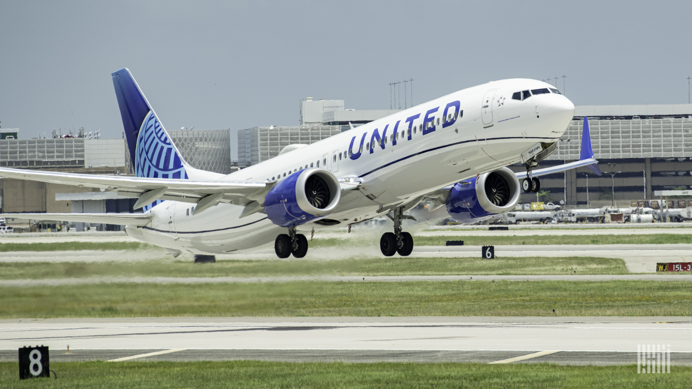 A white United Airlines jet with blue tail touches down on the runway.