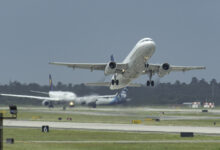 A white plane takes off with view facing the aircraft.