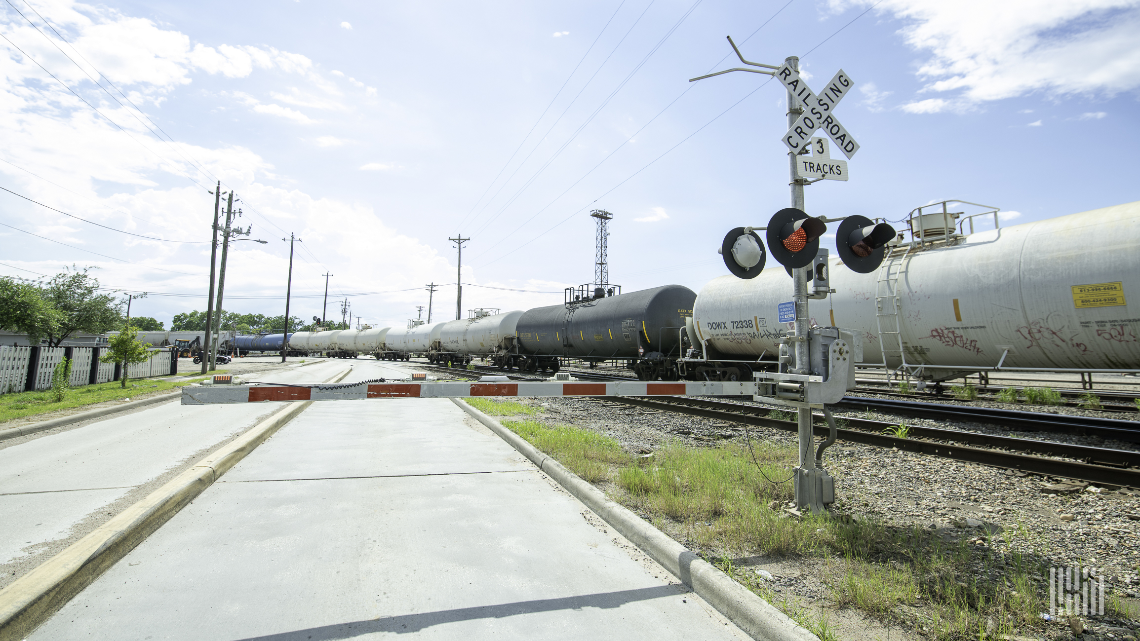 A photograph of a train of tank cars at a rail crossing.