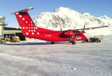 A turboprop plane on runway with snow-covered mountains in distance in Greenland.