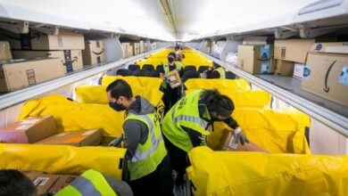 Workers put boxes in yellow seat bags in the passenger cabin of a plane.
