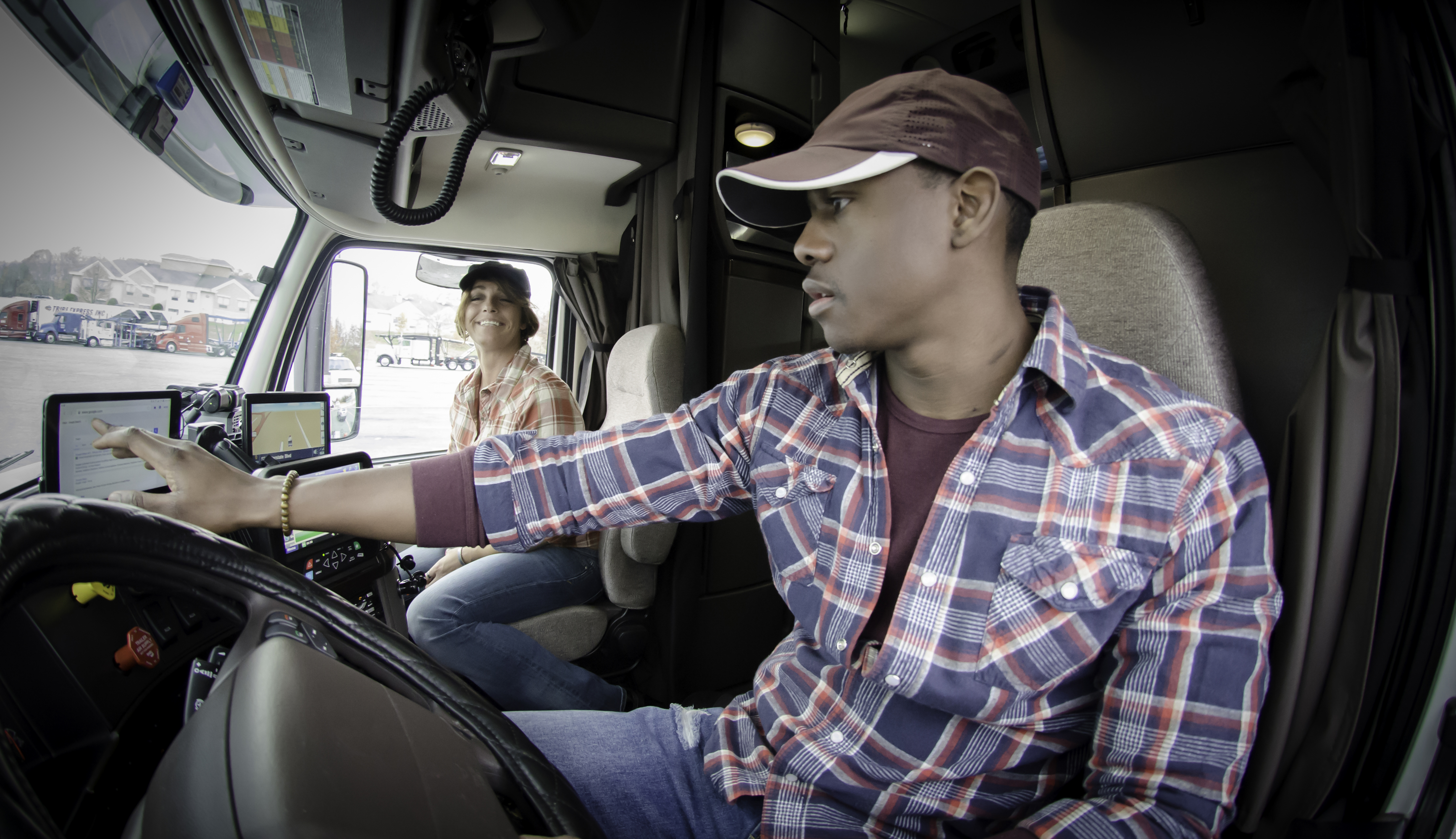 A male and female driver setting up apps inside the cab of their truck.