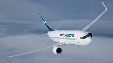 A white WestJet plane with aqua trim flying above the clouds and coming towards camera.