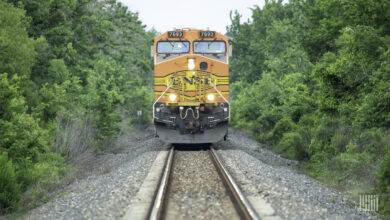 A photograph of a BNSF locomotive passing through a forest.
