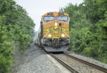 A photograph of a BNSF train rolling through a forest.