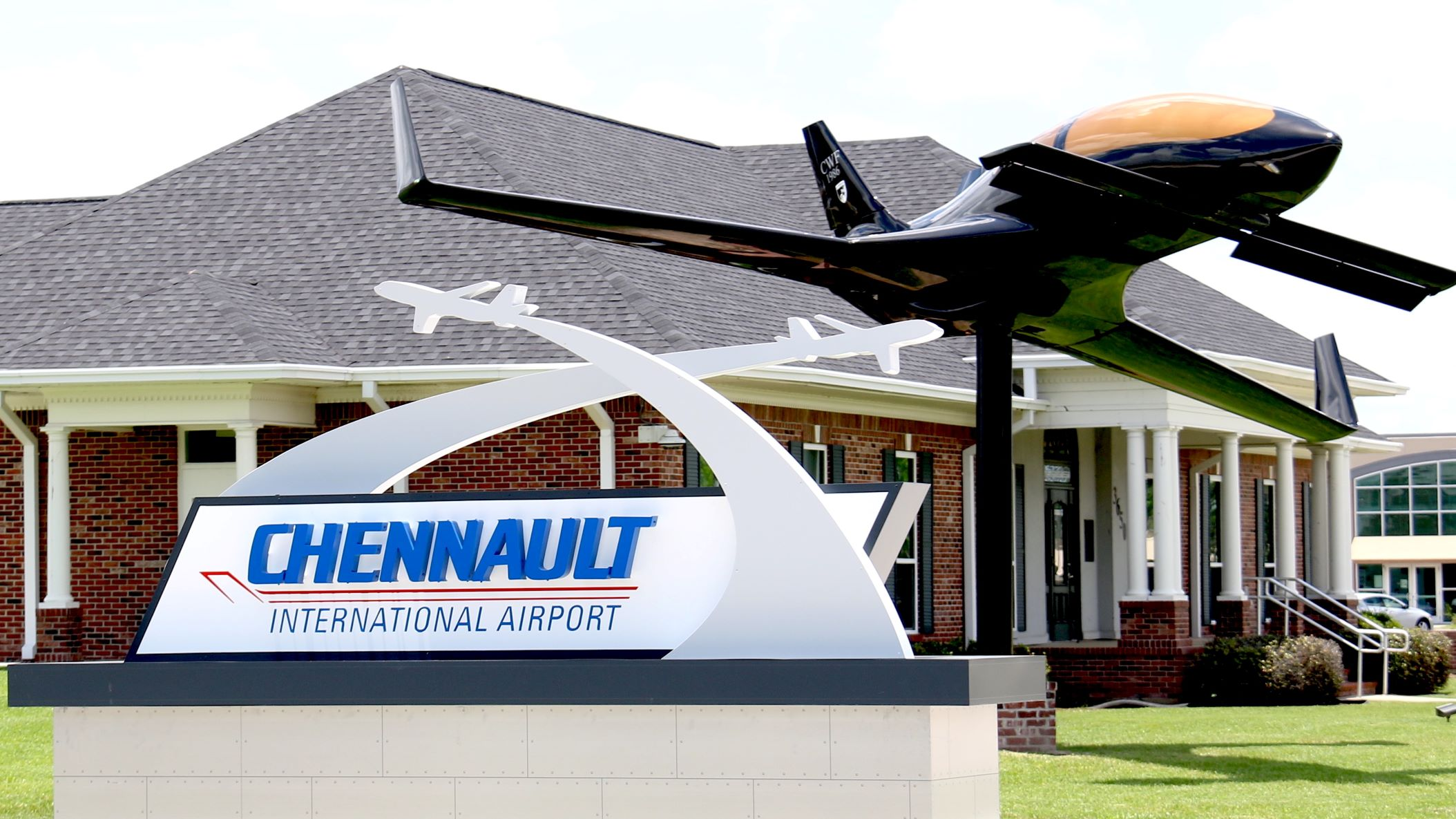 Entrance to Chennault International Airport, with sign and statue of a plane in front of small brick building.