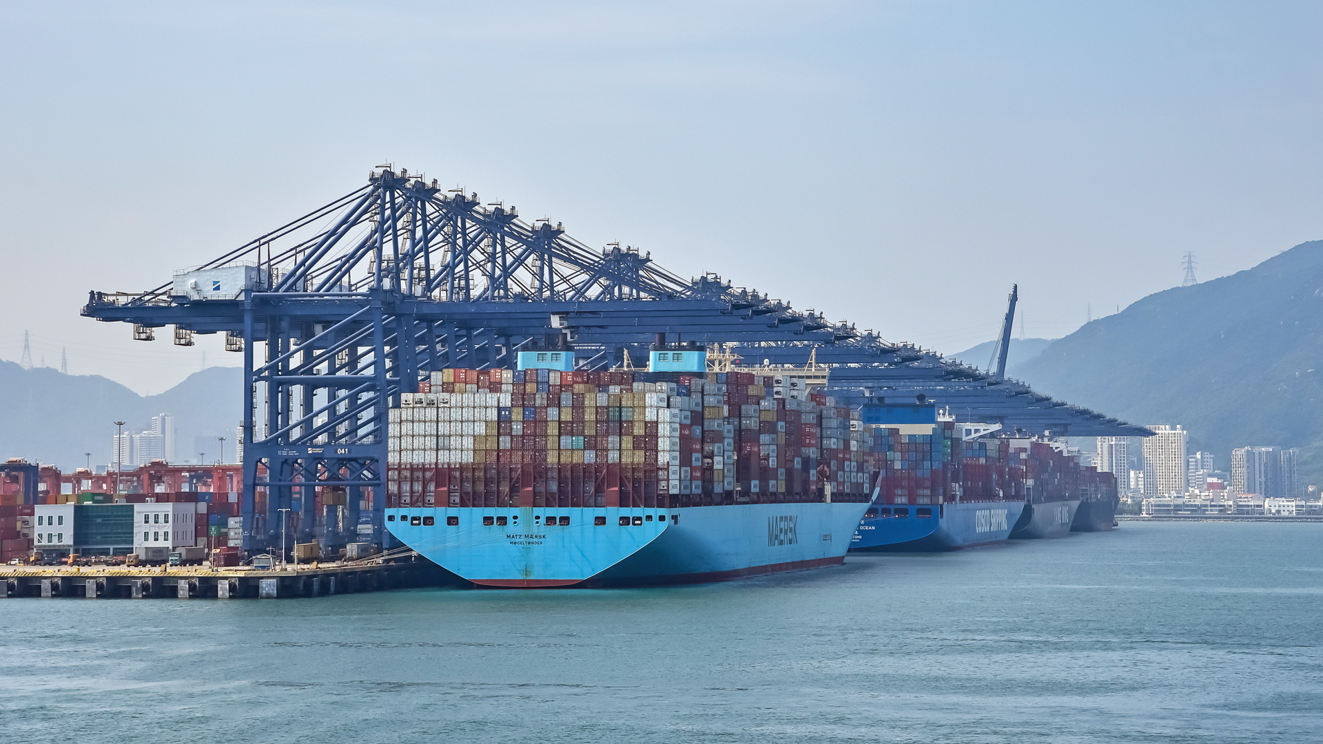 Three big container vessels in a row at a port terminal, with cranes overhead.