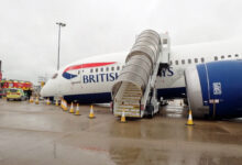 Side view of a British Airways airliner collapsed on its nose with stairs to cabin still attached.