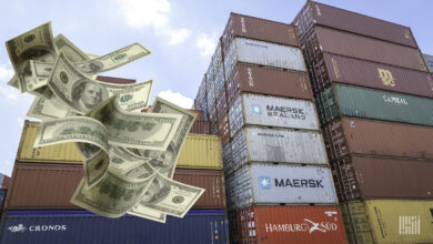 A stack of ocean freight containers with dollar bills added to image to show how expensive shipping has become.