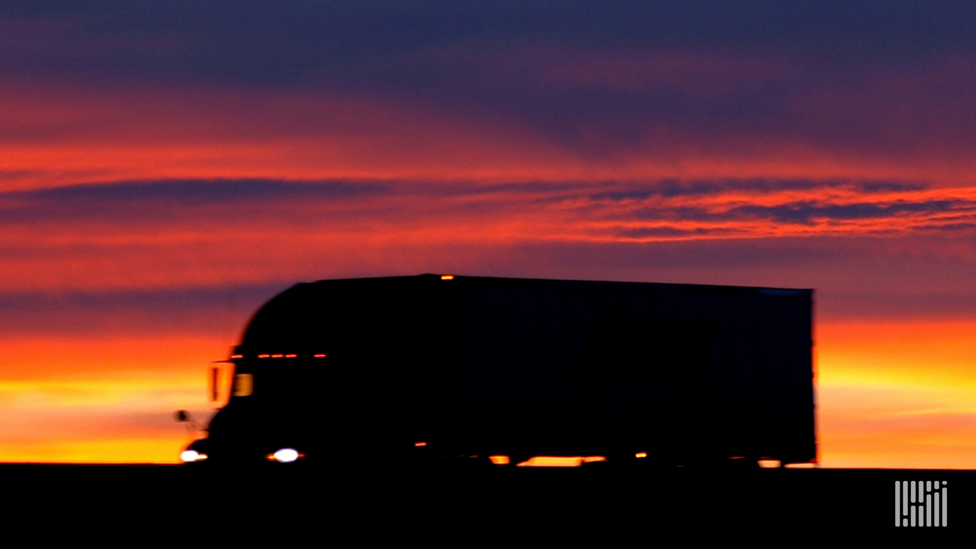 Tractor-trailer on a highway with hot sun on the horizon.