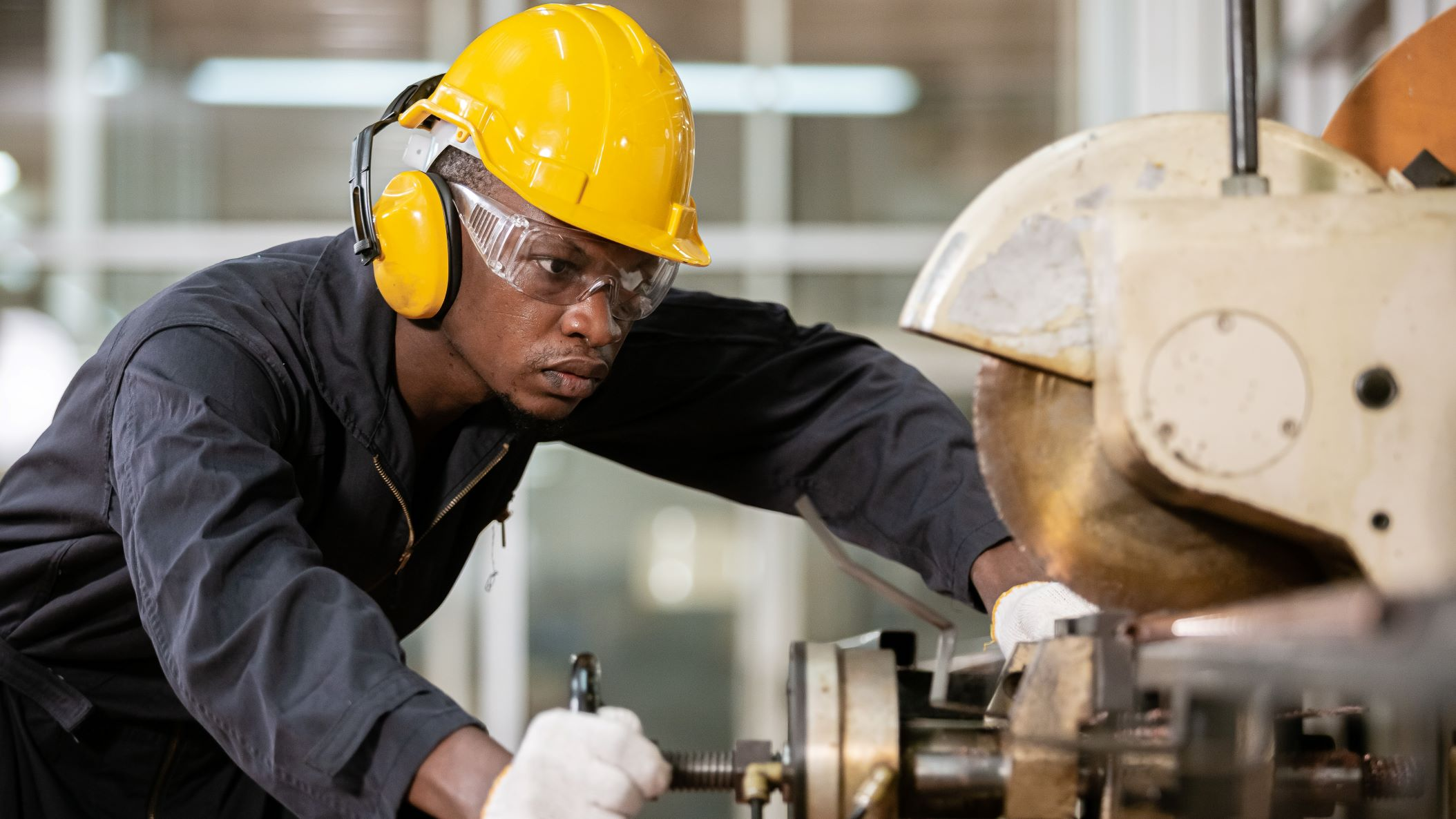 A black male wears soundproof headphones and yellow helmet working in an iron-cutting factory.