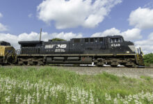 A photograph of a Norfolk Southern train rolling by a field.