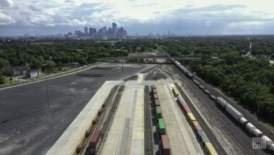 A photograph of a rail yard with a city in the distance.