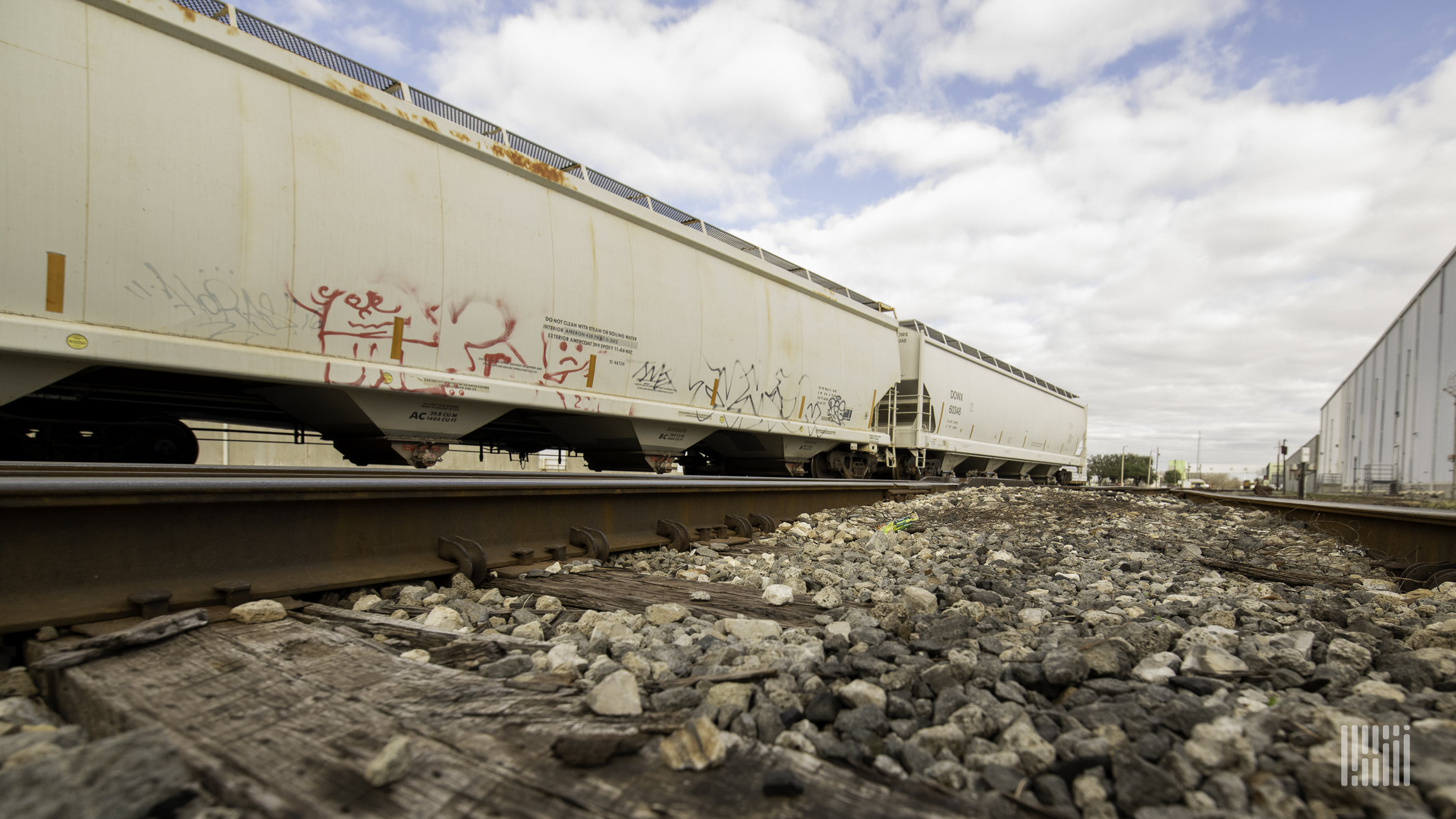 A photograph of trains of hopper cars sitting in a rail yard.