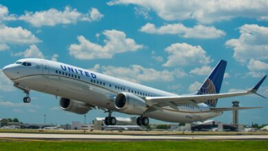 A United Airlines jet, with white fuselage and blue tail, lifts off from runway under bright blue sky with clouds.