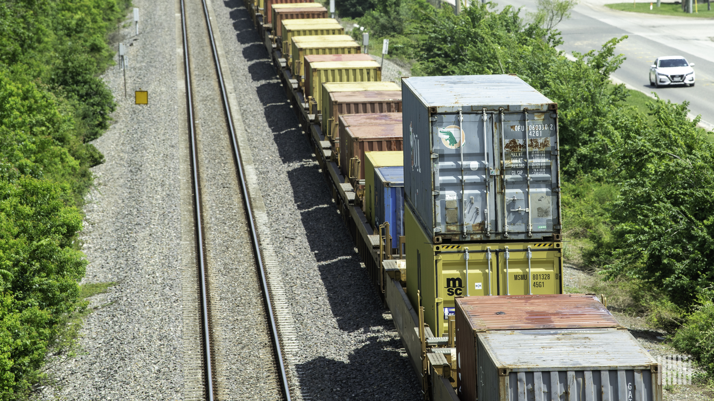 A photograph of intermodal containers being hauled by a freight train.