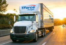 A white tractor-trailer TFI International carrier TForce Freight seen from the front travels on a highway as the sun sets behind it.