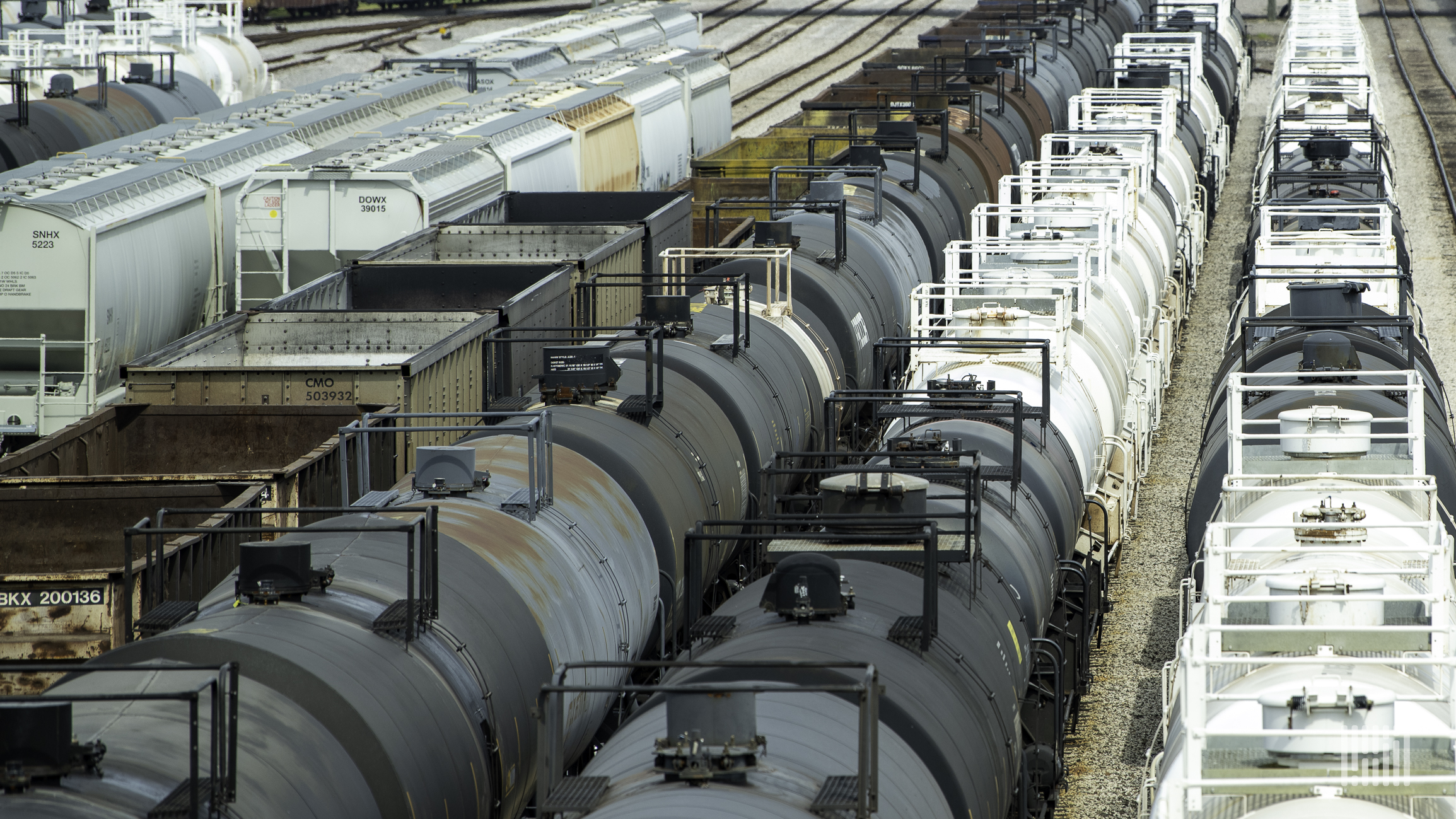 A photograph of a tank cars and grain hoppers parked in a rail yard.