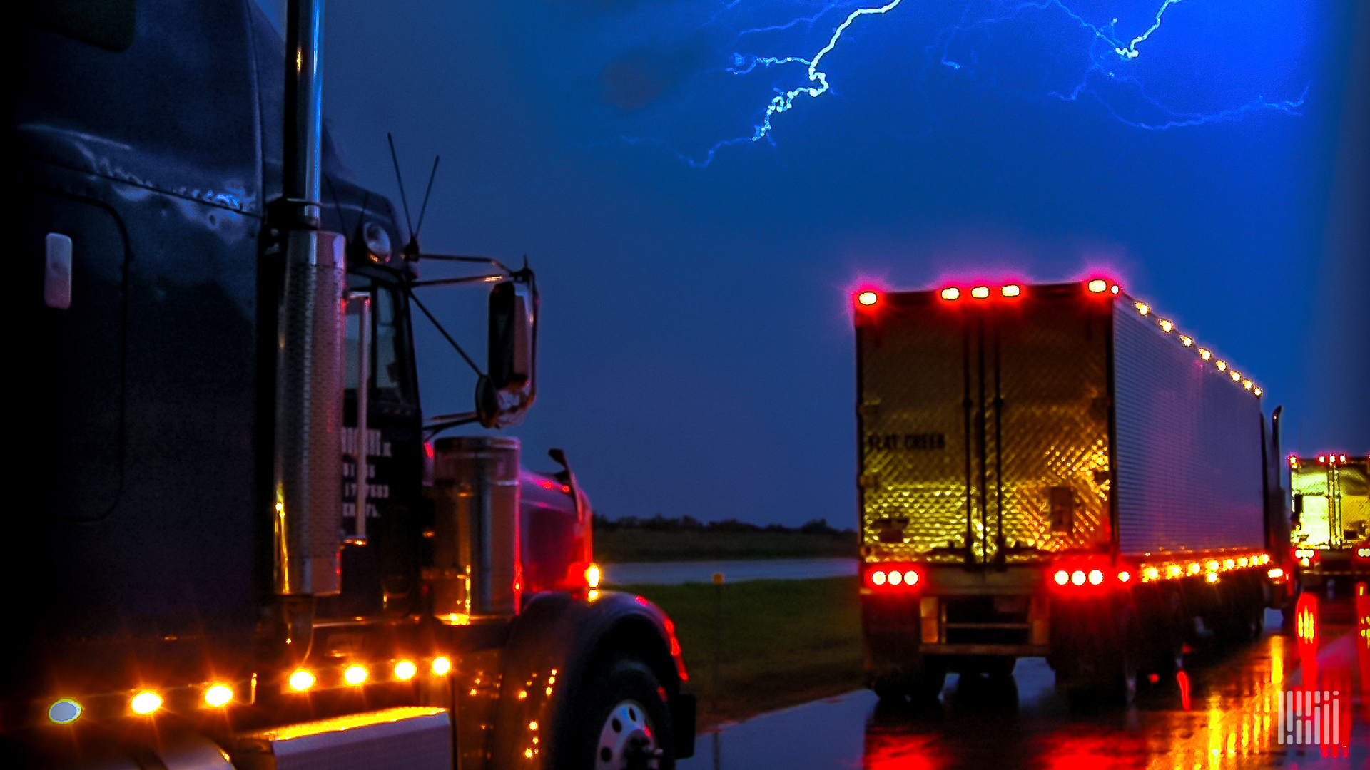 Tractor-trailers heading down wet highway with lighting across a night sky.