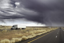 Thunderstorm behind a tractor-trailer on a highway.