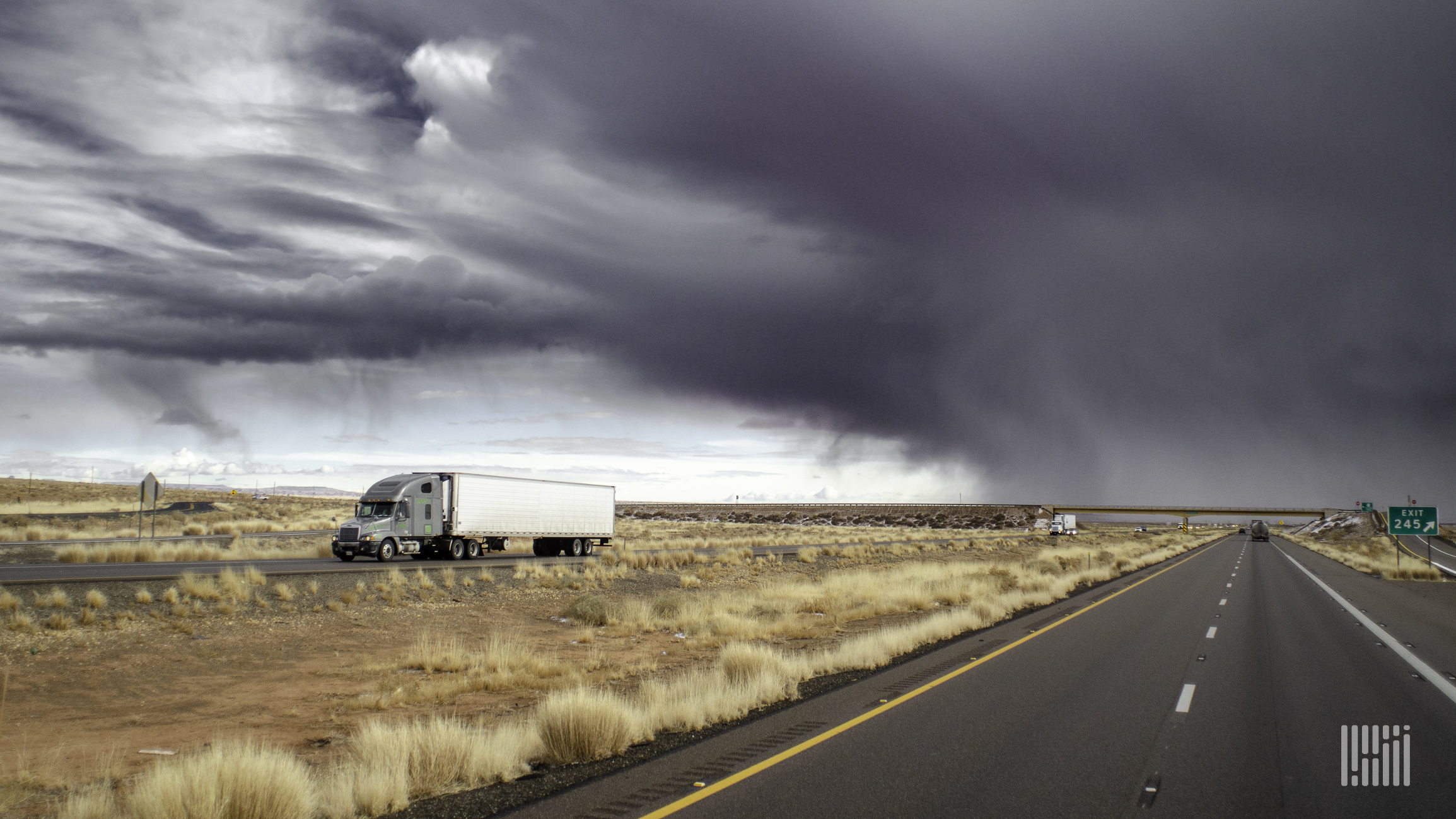 Tractor-trailer heading down a desert highway with storm cloud behind it.