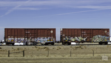 A photograph of two boxars rolling down train track.