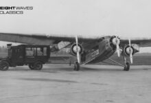 A Ford 5-AT sits on an airfield runway with its cargo door open, taking mail from a waiting mail truck. The large plane had three motors and a single wing across its top. National Postal Museum