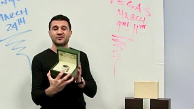 A man, All State Association CEO Steve Avetyan, holding a Rolex watch in front of a white board.