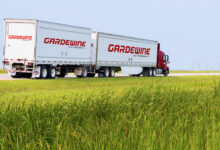 A red truck of Mullen Group carrier Gardewine pulling a double trailer, seen from the side.