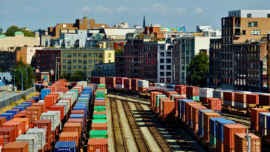 Rail cars loaded with intermodal containers near the port of Vancouver, with the city skyline behind it.