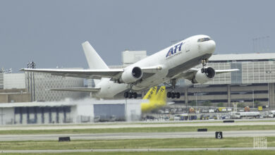 A big white jet with ATI lettering lifts off from runway.