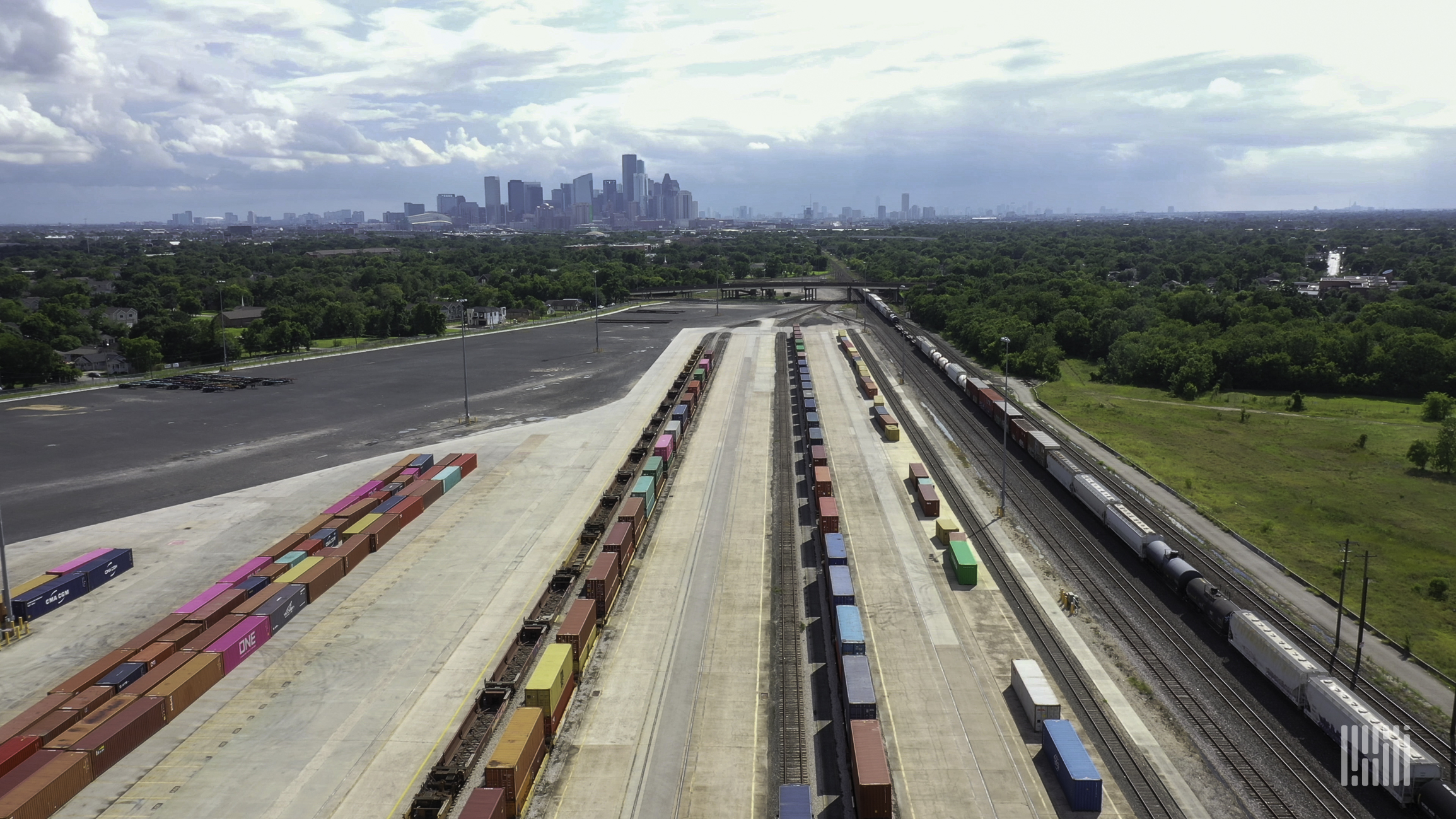 An aerial photograph of a rail yard with parked intermodal containers lined up in rows.