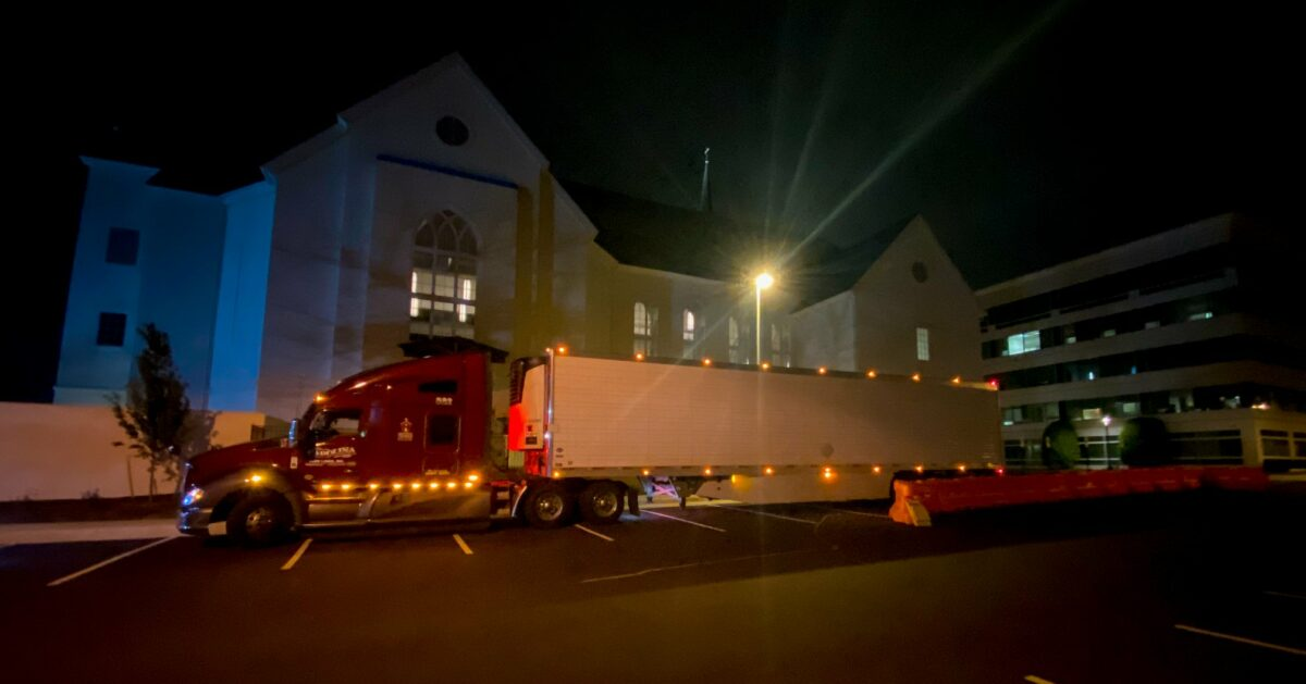 Truck in front of a church at night.