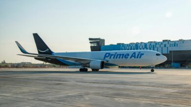 A white Amazon Prime jet with light blue accents rolls in front of a cargo building.