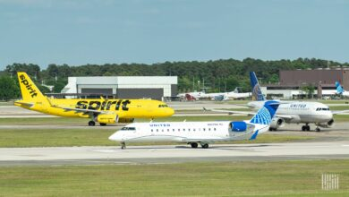 A yellow Spirit Airlines plane and two small United Airlines jets taxi around an airport.
