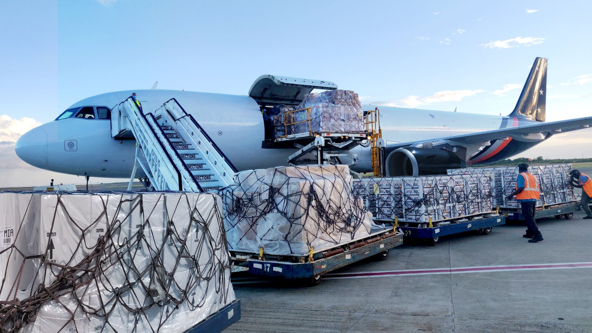 Ground-level view of cargo pallets on the tarmac being loaded on a white aircaft.