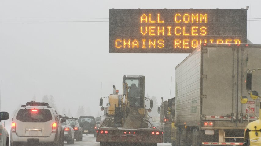 """""""Chains required"""" sign on a snowy Colorado highway."""
